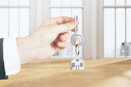 Businessman hand holding key with house chain in interior with city view and sunlight. Real estate concept. 3D Rendering