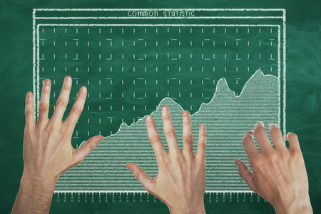 Abstract image of hands with drawn business chart on chalkboard background. Teamwork and analysis concept