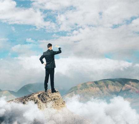 Back view of young businessman standing on mountain top and looking into the distance. Employment concept