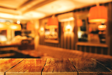 Abstract blurry restaurant interior wallpaper with empty wooden table. Mock up