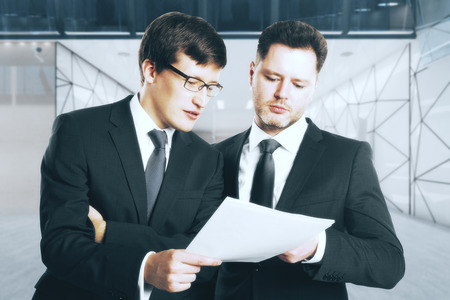 Portrait of two handsome businessmen discussing contract on blurry office workplace interior background. Teamwork concept. 3D Rendering Reklamní fotografie