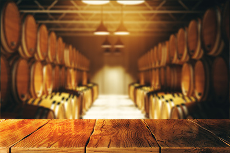 Close up of empty wooden table with blurry wine barrels in the background. Winery and alcohol concept. 3D Rendering Archivio Fotografico