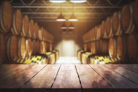 Close up of empty wooden table with blurry wine barrels in the background. Winery and beverage concept. 3D Rendering 免版税图像 - 89596132