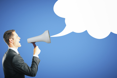 Side view of young businessman screaming into megaphone on blue background with empty speech cloud. Communication and loudspeaker concept Stok Fotoğraf