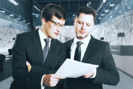 Portret van twee aantrekkelijke zakenlieden die contract op de onscherpe binnenlandse achtergrond van de bureauwerkplaats bespreken. Teamwork concept. 3D-weergave