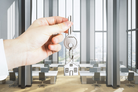 Close up of businessman hand holding key with house keychain on blurry coworking office interior background. Workplace and rent concept. 3D Rendering