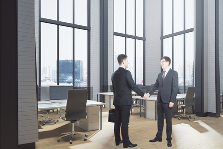 Cheerful european businessmen shaking hands in modern coworking office interior with equipment, panoramic city view and sunlight. Teamwork concept. 3D Rendering  Stock Photo