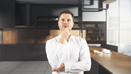 Nadenkende jonge zakenman die zich in modern onscherp keukenbinnenland bevindt. 3D-weergave