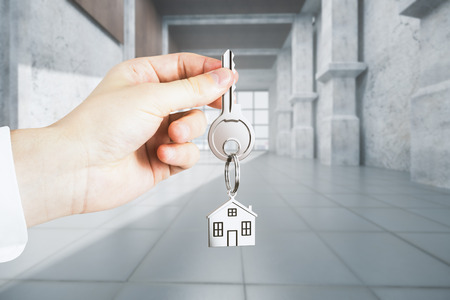 Businessman hand holding key with house keychain on abstract concrete interior background. Office and rent concept. 3D Rendering