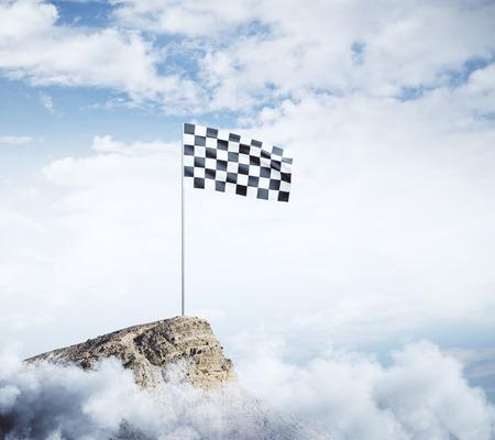 Checkered flag on mountain top. Cloudy sky background. Win concept  Stok Fotoğraf