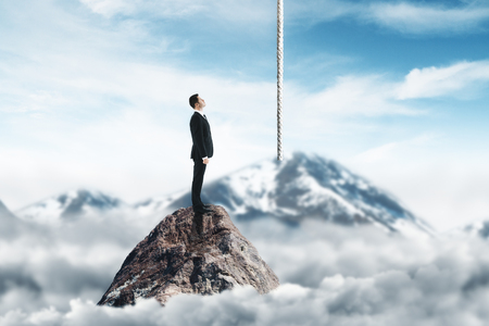 Side view of young businessman standing on mountain top and looking at rope on abstract blurry sky background. Leadership and solution concept Stock Photo