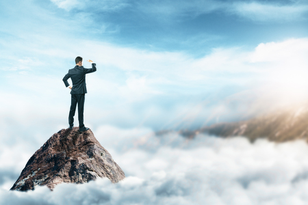 standing stone: Back view of young businessman standing on mountain top and looking into the distance on abstract cloudscape background. Leadership and research concept