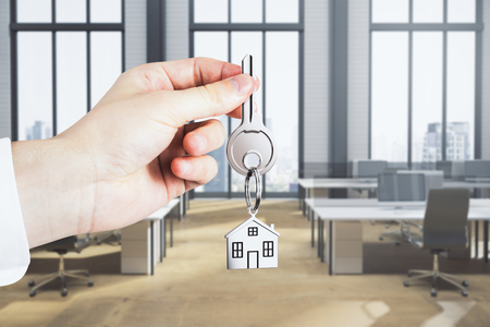 Close up of businessman hand holding key with house keychain on blurry coworking office interior background. Workplace and mortgage concept. 3D Rendering