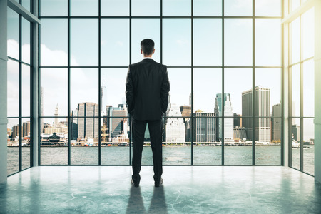 Back view of young businessman looking out of window in interior with city view. Success and research concept. 3D Rendering