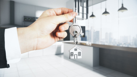 Businessman hand holding abstract key with house keychain on blurry kitchen interior background. Lifestyle and rent concept. 3D Rendering