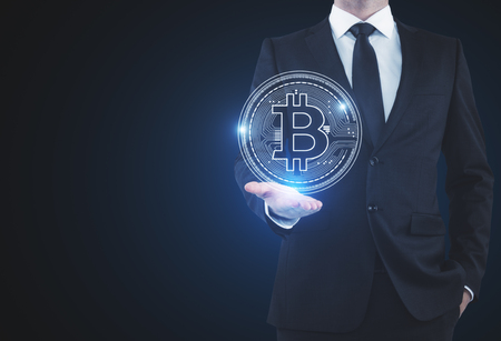 Businessman holding abstract glowing bitcoin sign on blue background. Online banking and payment concept. 3D Rendering Imagens - 90181756