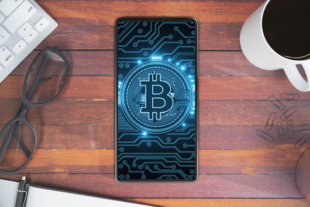Top view and close up of smartphone with bitcoin placed on wooden office desktop with coffee cup, glasses and other items. Communication and cryptography concept. 3D Rendering  Stock Photo