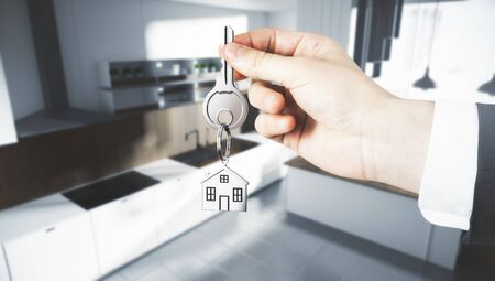 Businessman hand holding abstract key with house keychain on blurry kitchen interior background. Lifestyle and buy concept. 3D Rendering  Stock Photo