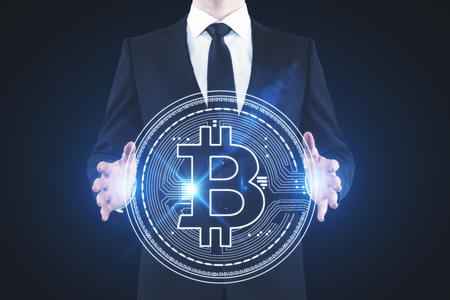 Businessman holding abstract glowing bitcoin sign on blue background. Online banking and cryptography concept. 3D Rendering