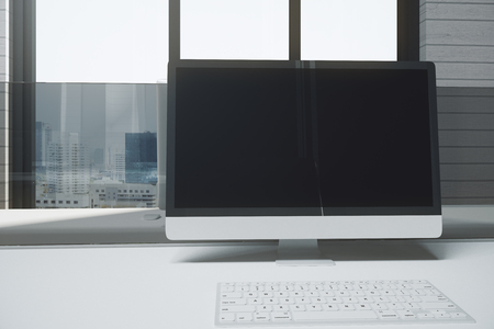 Close up of creative designer desktop with empty pc screen and keyboard. City view and sunlight background. Mock up, 3D Rendering  Stock Photo