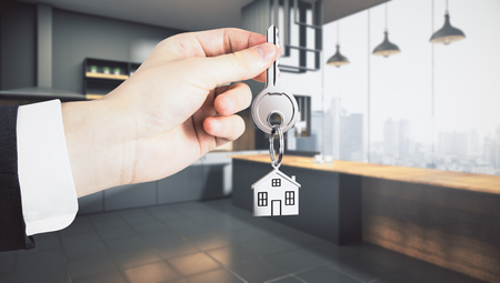 Businessman hand holding abstract key with house keychain on blurry kitchen interior background. Lifestyle and mortgage concept. 3D Rendering
