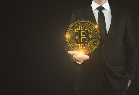 Businessman holding abstract glowing bitcoin sign on blue background. Online banking and e-business concept. 3D Rendering  Stok Fotoğraf