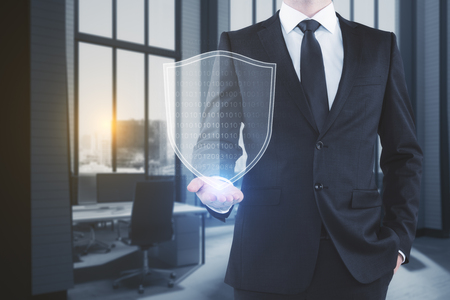Businessman holding glowing antivirus shield on blurry office interior background. Safety and software concept. 3D Rendering