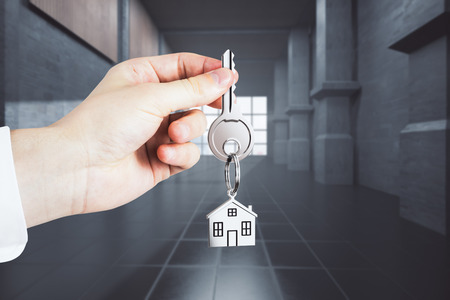 Businessman hand holding key with house keychain on abstract concrete interior background. Office and mortgage concept. 3D Rendering