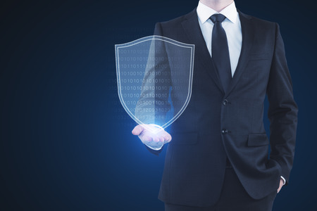 Businessman holding glowing antivirus shield on blue background. Safety and web concept. 3D Rendering  Фото со стока
