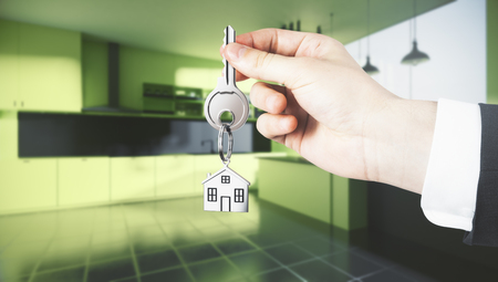 Businessman hand holding abstract key with house keychain on blurry kitchen interior background. Lifestyle and realtor concept. 3D Rendering  Stock Photo