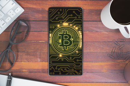 Top view and close up of smartphone with bitcoin placed on wooden office desktop with coffee cup, glasses and other items. Communication and payment concept. 3D Rendering