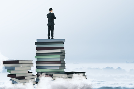 Back view of young businessman standing on abstract book pile and looking into the distance on cloudy sky background. Education and tomorrow concept. 3D Rendering
