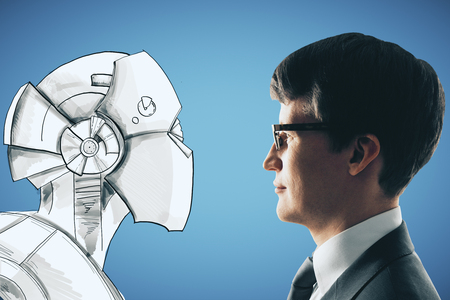 Side portrait of handsome young businessman facing drawn robot on blue background. Creativity and robotics concept  Stock Photo