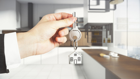 Businessman hand holding abstract key with house keychain on blurry kitchen interior background. Lifestyle and real estate concept. 3D Rendering