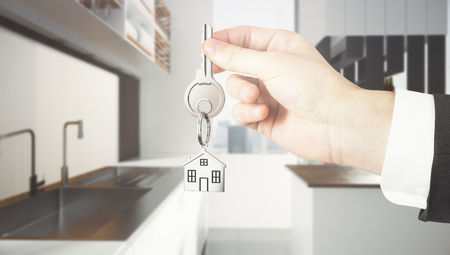 Businessman hand holding abstract key with house keychain on blurry kitchen interior background. Lifestyle and purchase concept. 3D Rendering  Stock Photo
