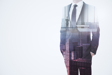 Unrecognizable businessman standing on abstract whte city background with copy space. Success and think concept. Double exposure