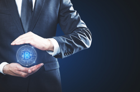 Businessman holding abstract glowing bitcoin sign on blue background. Online banking and web concept