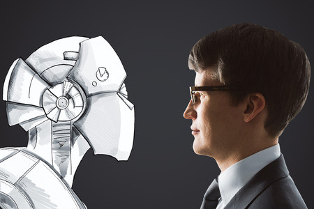Side portrait of handsome young businessman facing drawn robot on black background. Cyberspace and robotics concept  Stock fotó