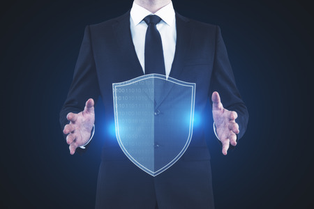 Businessman holding glowing antivirus shield on blue background. Safety and internet concept. 3D Rendering  Stok Fotoğraf