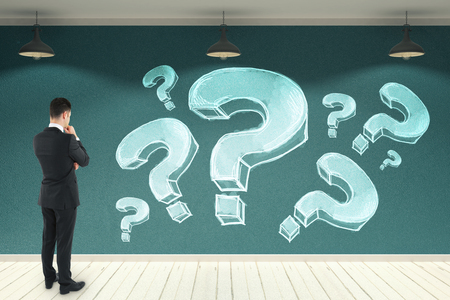 Young businessman looking at concrete wall with drawn question marks. Confusion and faq concept. 3D Rendering  版權商用圖片