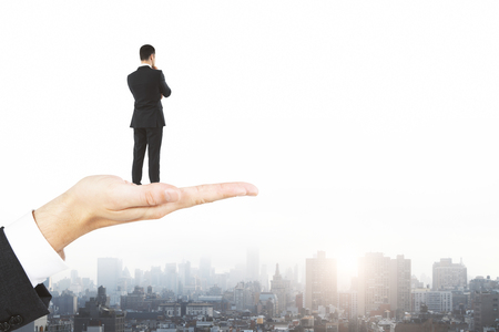 Abstract image of hand holding businessman on city background with copy space and daylight. Research and future concept