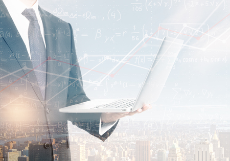 Unrecognizable businessman holding laptop on abstract city background with mathematical formulas. Technology and science concept. Double exposure