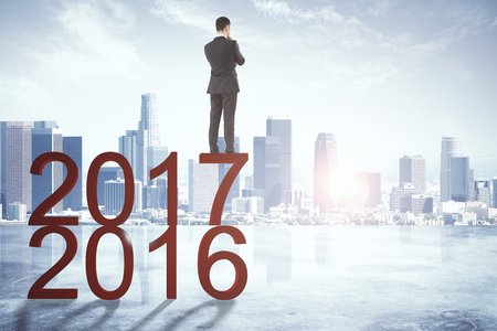 Back view of young businessman looking forward to new year 2018 on abstract city background with sunlight and copy space. Future and job concept