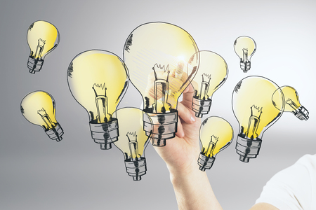 Man drawing yellow lamps on grey background. Innovation and idea concept Stock Photo
