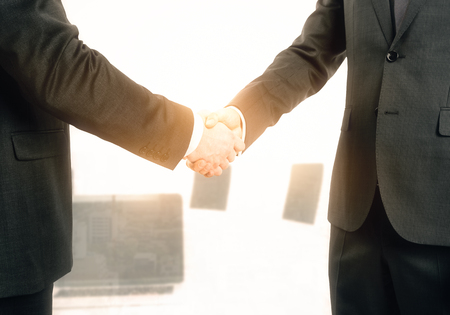 Side view of handshake on abstract blurry bright office background. Teamwork and union concept  스톡 콘텐츠