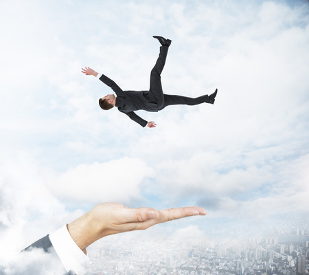 Hand ready to catch falling businessman on cloudy sky background. Assistance and trouble conceprt
