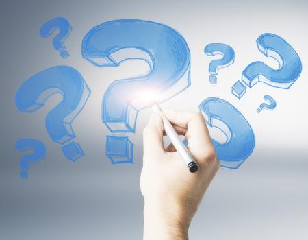 회색 배경에 파란색 물음표를 그리기 남성 손. FAQ 및 조회 개념 스톡 콘텐츠