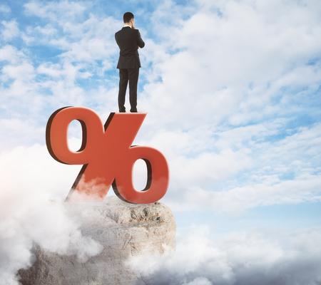 Homme d & # 39 ; affaires debout sur le signe abstrait de pourcentage rouge sur fond de ciel . concept de l & # 39 ; économie Banque d'images - 91782244