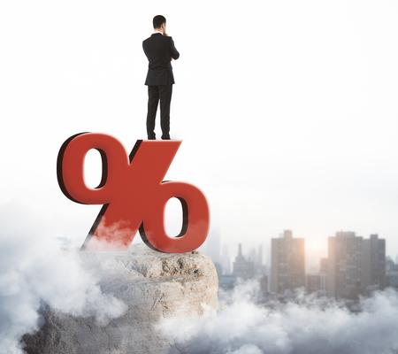 Homme d & # 39 ; affaires debout sur le signe abstrait de pourcentage rouge sur fond de ciel . concept de l & # 39 ; économie Banque d'images - 91525726