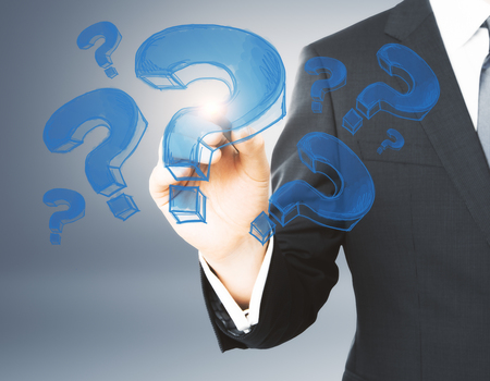 Businessman hand drawing blue question marks on gray background. FAQ and ask concept  Stockfoto